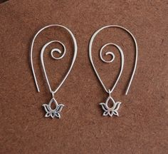 Earrings sterling silver lotus charms and hammered spiral sterling silver ear wire. 28.00, via Etsy.