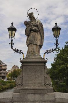 Sint-Johannes Nepomucenus. Opschrift: aan de arbeiders schonk mij Leonard Jozef Surmont 1749 - vijandschap schond mij 1798 - Hendrik Nolf herstelde mij 1853 - van de grote brug naar de linkeroever van de Leie werd ik verbannen 1882 - naar de Broelbrug werd ik overgebracht 1913 - tweemaal stortte het oorlogsgeweld mij in het water 1918 en 1940 - telkens bracht de vrede mij op de wederopgebouwde brug 1922 en 1960 Plaatsbeschrijving: Kortrijk - Op de brug over de Leie, tussen beide Broeltorens