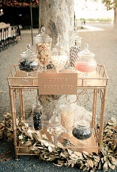 A vintage wedding wouldn't be complete without an antique bar cart. But instead of using it to serve cocktails, use it to showcase a candy bar. Fill glass hurricanes and vases with candy so guests can nibble on sugar throughout the reception. Photo by Wedding Artists Collective via 100 Layer Cake
