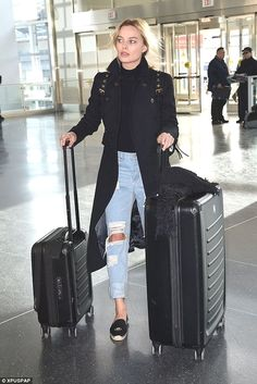 25358ac26a4a Airport Style glamhere.com Wearing ripped jeans a black turtleneck and navy  coat with canvas