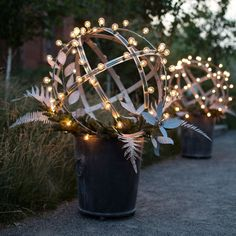 A stately iron planter becomes a year-round fixture when topped with an illuminated garden structure. Affix a strand of Stargazer Globe Lights to the Christmas Porch, Outdoor Christmas Decorations, Christmas Holidays, Holiday Decor, Christmas Garden, Holiday Lights, Christmas Lights, Wine Barrel Rings, Garden Spheres