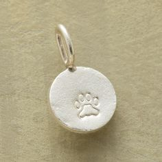 PAWPRINT CHARM�--�Lightly oxidized, textured sterling silver disk stamped with a puppy pawprint. Made in USA. 5/8 dia.