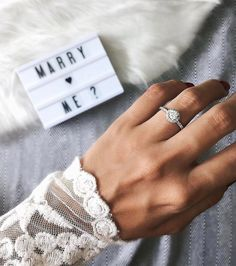 A mini-marquee and halo engagement ring make for a totally dreamy post-proposal selfie.
