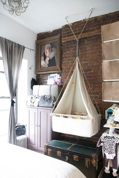 In the tiniest apartments, every square inch counts. And this hanging bassinet, suspended over a storage-boosting antique trunk, is just one genius space-saving idea in this NYC couple's stylish (if small) abode.
