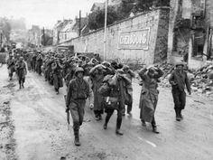 Photograph:German prisoners are marched out of Cherbourg, France, by U.S. soldiers, June 1944.