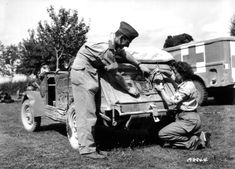 'Rochambelle' Edith Vézie, Free French Nurse attached to the 2nd French Armoured Division, stencils the divisional insignia (the Cross of Lorraine) on this captured Kübelwagen. In the background is a Dodge WC54 ambulance. Picture taken in the commune of Écouché, which was liberated on the 13th of august 1944, by the 1/501 Régiment de Chars de Combat, which remained in reserve in the area until the 23rd when it moved to Paris.