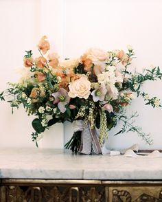 Sarah Winward of Honey of a Thousand Flowers used the mauve-champagne and taupe textiles at the Utah wedding venue as inspiration for this bouquet, which included hellebores, ranunculus, sweet pea, pieris, spirea, poppies, and champagne roses.