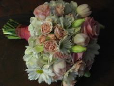 Pink double tulips, pink roses, white daisy, lisianthus, and hydrangeas