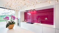 Sometimes there's an image that just captures your attention and you are instantly in awe - like this kitchen design displaying major wow factor. A shiny pink backsplash against the clean white linear kitchen. The orchid ties in perfectly and that funky, yet delicate chandelier is quite something. This kitchen shows that modern minimal need not be boring and cold.  #kitchen #interior #pink