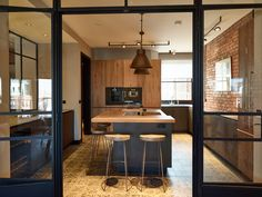 The atelier style doors and windows are perfect to open the kitchen onto other rooms. Concept by P&P Interiors.