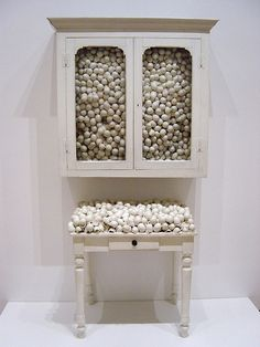 "Marcel Broodthaers. White Cabinet and White Table. 1965. Painted cabinet, table, and eggshells. Broodthaers often used found or discarded materials, favoring eggshells, which are ""without content other than the air."" Using antique-looking furniture and organic materials, Broodthaers critiqued museum display and avoided modern products. In 1968, he created his own museum—called Museum of Modern Art—in his apartment, complete with labels and a catalogue."