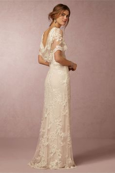 Estella Gown. A lacy illusion boatneck, flutter sleeves, and a stunning cowl-back make this delicately beaded column gown an elegant gem. Soft bisque lining accentuates ivory lace for just the right amount of subtle romance and chic allure.
