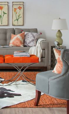 Vibrant orange accent pieces on a grey palette.