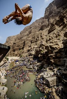 Cyrille Oumedjkane of France clutches his legs as he makes the death defying jump, before hitting the water at 85kph - Red Bull Cliff Diving World Series 2012, Wadi Shab, Oman
