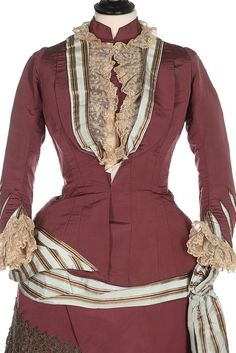 A Charles Frederick Worth visiting dress, circa 1875. the jacket-like bodice with ivory waist stay printed in gold 'Worth, 7 Rue de la Paix, Paris', of puce silk faille trimmed with pale blue silk with gold satin stripes, the lapel bands and cuffs inset with ivory lace, the sleeves with slash-effects at the cuffs revealing striped silk, the rear basque tails with off-centre bow and ribbons; the skirt with draped striped ribbon bands, with rich tasselled gold passementerie to the puce side…