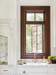 A classic kitchen combo that will never go out of style: Crisp white cabinets, Calacatta marble, rich wood trim and aged brass hardware and faucets.