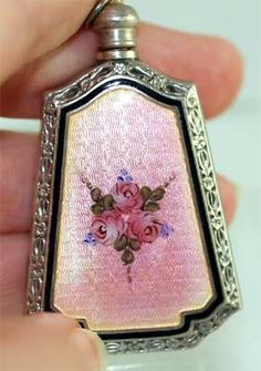 Edwardian Sterling & Pink Enamel Perfume Very ornate Edwardian era perfume, done in sterling and decorated with the prettiest shade of pink enamel! Accented with a fancy engraved sterling edge, then a border of black enamel and a center floral design to the front.