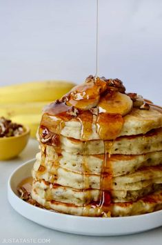 Stack of Banana Nut Pancakes topped with fresh banana slices, pecans and maple syrup; bananas and small bowl with pecans in background