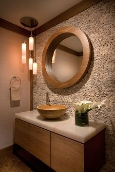 bathroom with natural stone walls and wooden bathroom vanity and mirrir <3