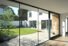 Floor to ceiling glazing in garden room with aged oak floor. New home with walled courtyard garden by McCann Moore Architects Belfast. Roof Window, Window View, Passive Design, Rear Extension, Belfast, Nice View, Architects, Garden Ideas, New Homes