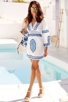 Breezy and beautiful with blue embroidery details on the front, the split flare sleeves and hemline, you&#8217ll want to wear this cotton cover-up for your next exotic getaway