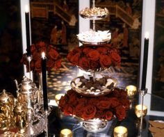 Three tiers of chocolate and vanilla treats are separated by layers of vibrant red roses.