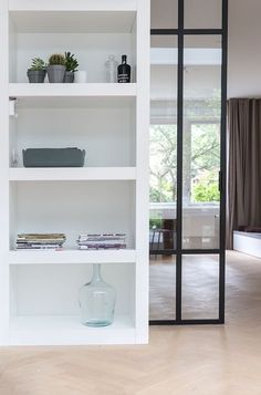 Love the black door that slides into the wall, herringbone flooring and shelves.