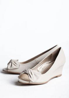 "Country Estate Bow Wedges 42.99 at shopruche.com. These faux leather wedges in cream are polished with a subtle bow detail and polished allure.All man-made materials, 2.25"" heel"