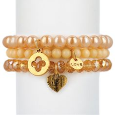 """Gold glass bracelet set of three with gold di-cut clover, angle wing heart, and love charms.  Measures approximately 7.5"""" in length. With the purchase of this bracelet set, 25% of gross profit goes to the Fisher House Foundation."""