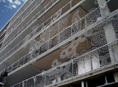 Embroidered chain link used artistically & functionally to decorate the side of this multi-story housing complex and provide a safety barrier at the railing.