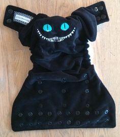 Little Beasties one size cloth pocket diaper with adjustable elastic & leg gussets; cat face embroidery; snaps.  From LittleBeastiesDiaper on Etsy.com $19.50.   I love, love, love this Cheshire Cat design!