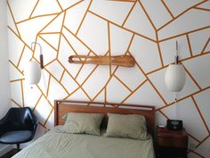 Really smart method by Alecia Stenseth of using painter's tape to get this geometric pattern. Hand paint the lines, cover in painter's tape, then paint over the tape in the same color again to prevent bleeding, then paint over everything in white (4 coats), and finally peel away tape to expose the design underneath.