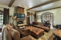 Masculine family room design with oversized sofas, large leather ottoman, exposed wood ceiling beams, room-sized rug and TV mounted above the fireplace