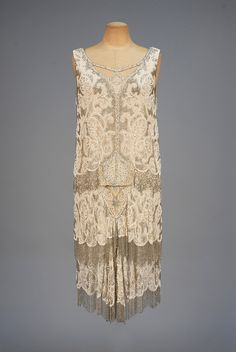 BEADED and FRINGED FLAPPER DRESS, 1920s. Sleeveless cream silk chiffon having cutout neckline decorated with pearls, rhinestones, white and crystal beads, bodice and tiered skirt fringed in crystal beads, chiffon under-dress with lace hem band. Whitaker Auctions, Fall 2015