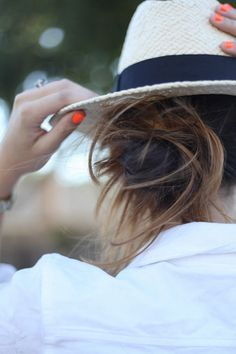Orange summer nails and beach hat over a messy bun