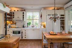 Kök med platsbyggd skåpsinredning och vedspis under murkåpa
