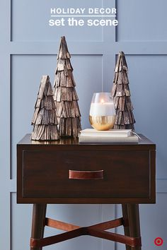 Refresh the look of any accent table by switching out the décor pieces each season. This Christmas, mixing charming woods and gorgeous metallics creates the perfect balance of rustic warmth and elegance. Top the table and make a statement by grouping Threshold wood/gold trees in odd numbers — conveniently, they're available in three different sizes! Then, add a soft glow with an opulent gold-base candle. This is an easy way to add a little holiday flair throughout your home.