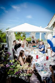 The wedding guests sit down for the wedding breakfast out on the terrace at Beacon House.