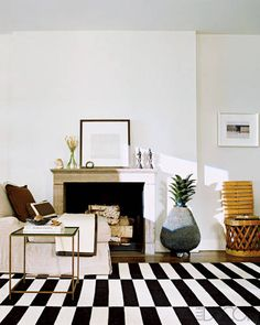 An 18th-century limestone mantel and linen-clad chair by Berkus; the side chair and ceramic pineapple are Mexican.