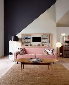 graphic effect of Black back wall + white half wall in front + simple pink sofa - nice rug texture - warmth brought in by wood tones and rug