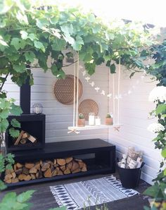 Leuk hoekje in de tuin met haard, houtopslag en een plantenschommel. Zwart, wit en hout.
