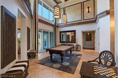 Formal living room turned game room - billiards anyone?  Love those pendant lights!!!  Luxurious Family Home for Sale in Banyan Woods | North Naples, Florida