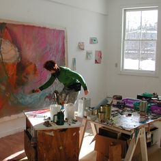 Artist painting on unstretched canvas in her art studio with natural light.