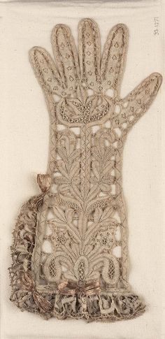 Woman's bobbin lace glove about 1650–1700 Main design is a conventionalized plant form. Brides connect with outline of glove. Double ruffle along top and half one side of glove. Remains of faded stiff pink ribbon bows (trimming).