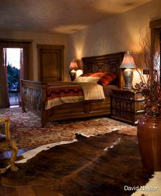 The master bedroom furniture is made from mahogany, pearwood, and walnut. The Western bedding is by Daniel Stewart of Santa Fe and Toronto. The strong Persian rug, the Western-inspired bedding, and the cowhide find unexpected cohesion in this design.