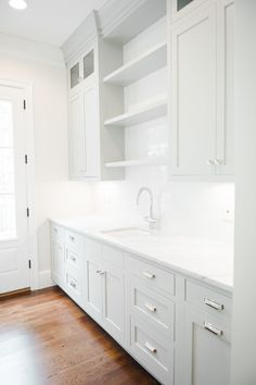 White kitchen with warm floor accents and polished nickel hardware