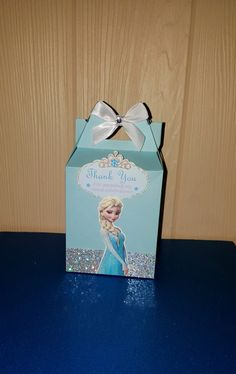 Frozen Elsa Favor Boxes  The perfect favor box for a candy buffet! P A C K A G E S: Groups of 6 or 12 boxes  S T Y L E: Medium Tall Gable Size: 6 inches total Height x 3.25 inches wide x 2 inches on the sides C H O O S E: **Frozen Elsa- Light Blue Box, Glitter Trim, White bow. Includes Image of Elsa and thank you message. A S S E M B L Y: Box will ship flat but will not require any adhesive to assemble, only simple tab tucking. PERSONALIZATION: Is not included in this listing but can be…