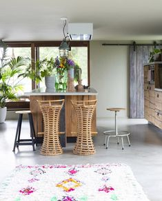 BINNENKIJKEN • in een levendige keuken gemaakt van oude Amsterdamse meerpalen aangekleed met rieten krukken en een gekleurd vloerkleed | kitchen with timber cabinets, wicker stools and colored carpet | vtwonen 9-2019 | Fotografie Jeltje Fotografie #kitchen #timber #wicker #binnenkijken