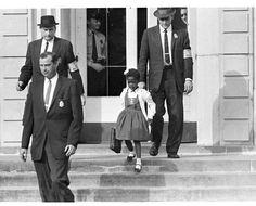 U.S. Deputy Marshals escort six-year-old Ruby Bridges from William Frantz Elementary School in New Orleans, La., in Nov. 1960. The first grader is the only black child enrolled in the school, where parents of white students are boycotting the court-ordered integration law and are taking their children out of school. (AP Photo)