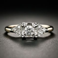 """Found on LangAntiques $1,250  """"This 1950s vintage diamond engagement ring, crafted in two-tone yellow and white gold, glistens with a bright-white, transitional round brilliant-cut diamond, weighing one-fifth-of-a-carat, but which presents significantly larger due to its illusion setting. The diamond is embellished on each side with a twinkling trio of single-cut diamonds set in a triangular arrangement. A very lovely traditional vintage engagement ring."""""""
